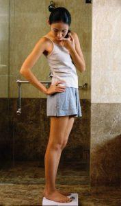 Slim Asian girl weighing herself